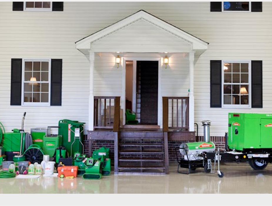 Infront of a house there is drying equipment, cleaning products, commercial generators